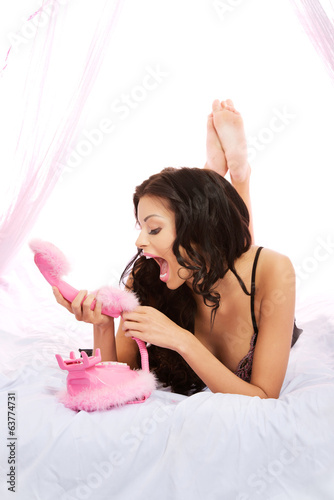 Sexy woman with pink phone on bed