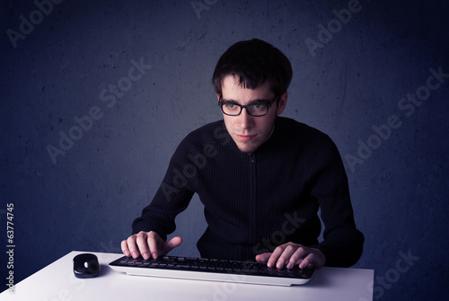 Hacker working with keyboard on blue background