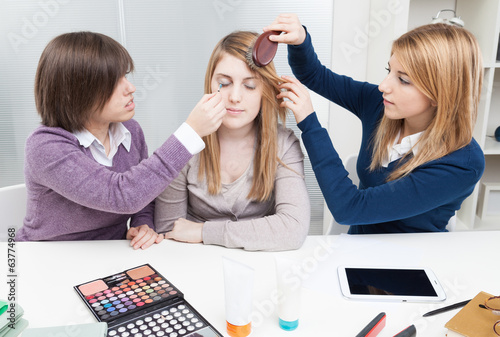 Three teenage girls applying a make-up