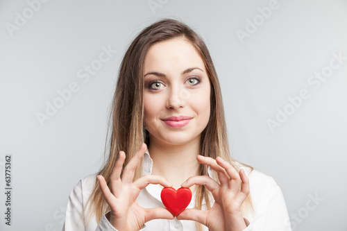 Portrait of a cheerful female  holding a heart.