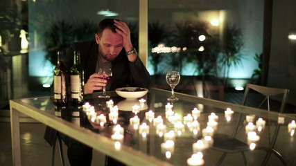 drunk man sitting by the table and drinking wine after unsuccess