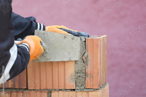 Mason working with trowel and cement