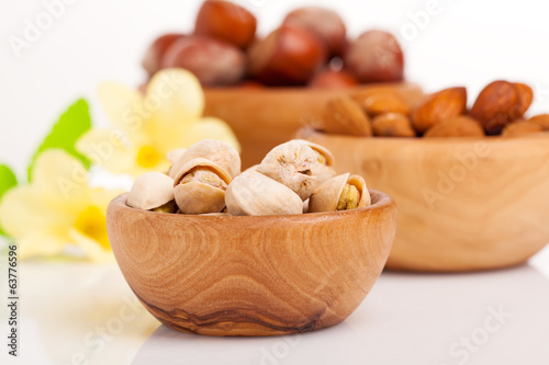 Pistachio, almonds, hazelnut with flowers in the wooden bowl.
