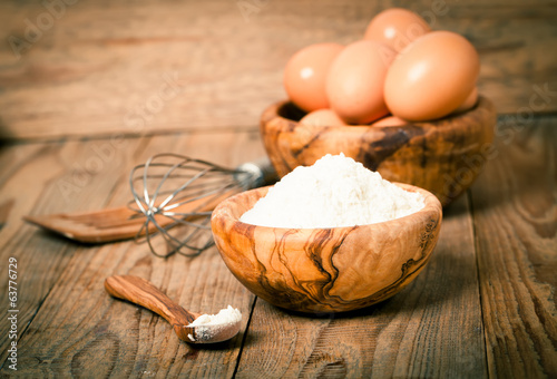 flour and eggs, ingredients for baking. on wooden background