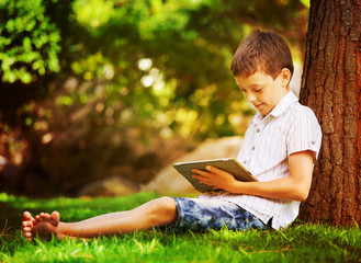 Boy on grass with tablet computer