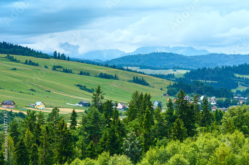 Summer cloudy mountain village view (Poland)