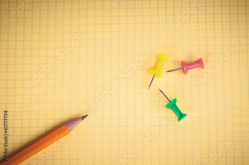 Pen and thumbtacks on yellow sheet of paper