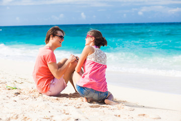 young happy couple in sunglasses sitting on tropical beach