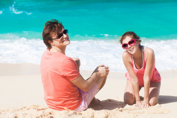 young happy caucasian couple in sunglasses sitting on tropical