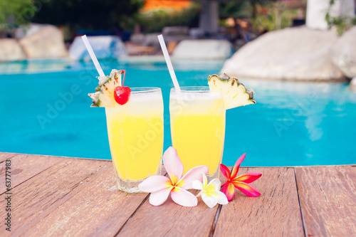 two glasses of bright cocktails and flowers near pool. party