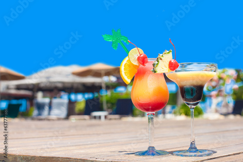 two glasses of bright cocktails near pool on clear blue sky