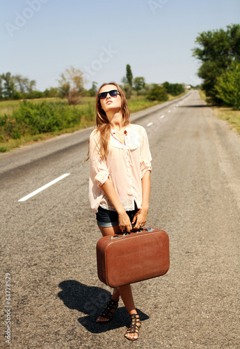 Pretty young woman with suitcase, hitchhiking along