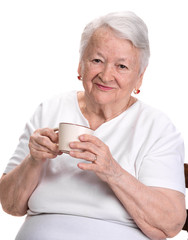 Old woman enjoying coffee or tea cup