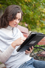 Woman using tablet computer park