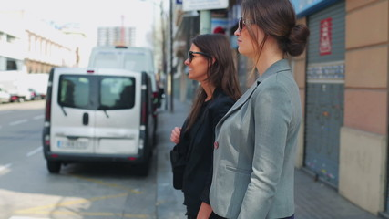 Businesswoman crossing street and talking, steadycam shot