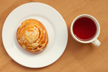 bun and cup of tea on tray