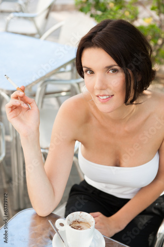 Woman smokes cigarette outdoor cafe