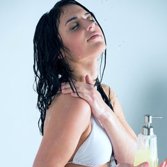 Beautiful girl showering. Holding glass bottle with shower gel