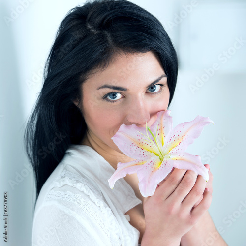Attractive young woman holding a lily flower