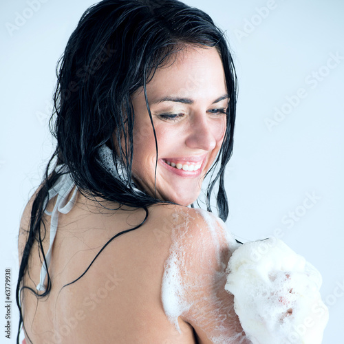 Young woman washing body with shower gel