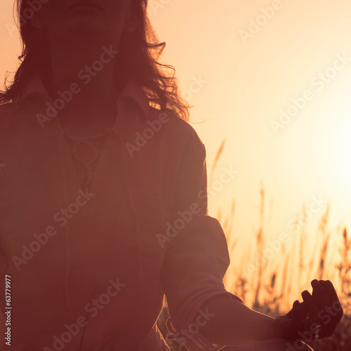 Beautiful Yoga woman siting against sunrise