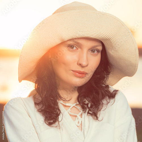 Woman wearing straw hat smiling and having fun against sunset an