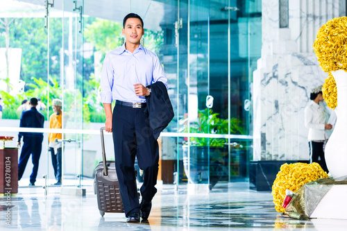 Asian man pulling suitcase in hotel lobby