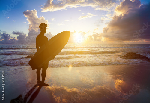 surfer man standing on beach and holding a surfboard