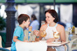 Little boy and mother eating ice-cream in cafe