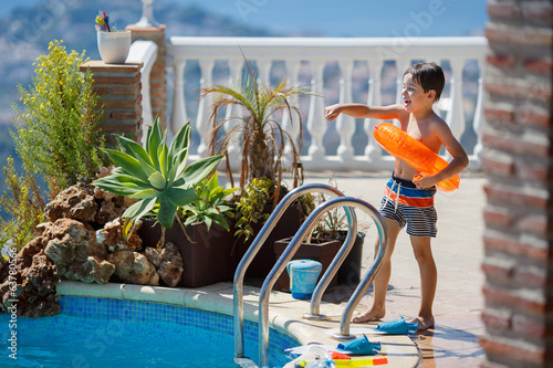 Little boy with swimtrainer near swimming pool