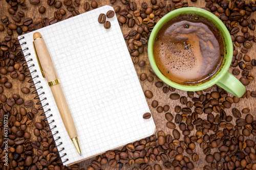 Notebook pen and cup of coffee