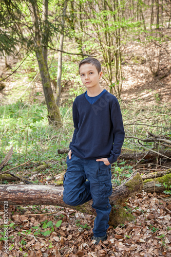 Good looking boy standing in a forest