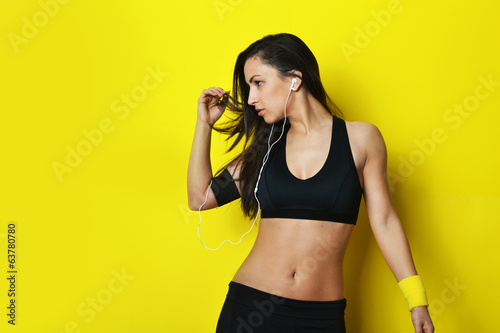 beautiful fitness woman dancing against the yellow background