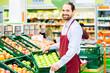 Leinwanddruck Bild - Supermarkt Angestellter füllt Regale auf
