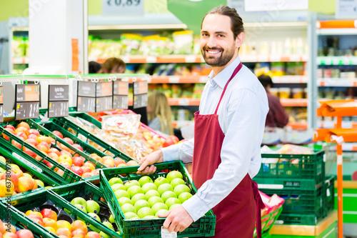 Leinwanddruck Bild Supermarkt Angestellter füllt Regale auf