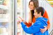 Family wählt am Supermarkt Tierfkühlregal