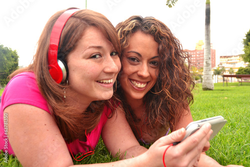 Friends listening music in park