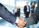 Business associates shaking hands in office poster