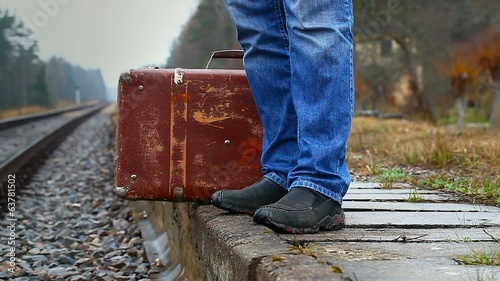 Man with a suitcase on the platform at the railway
