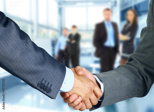 Leinwanddruck Bild Business associates shaking hands in office