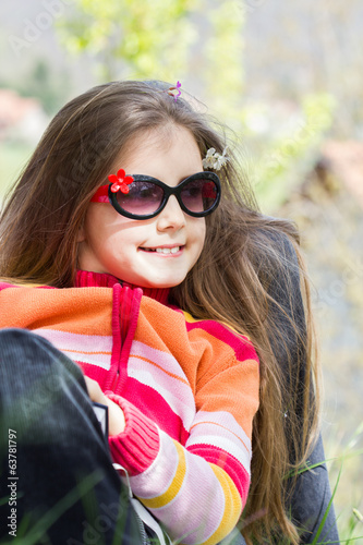 Cute little girl sits in a park holding a book