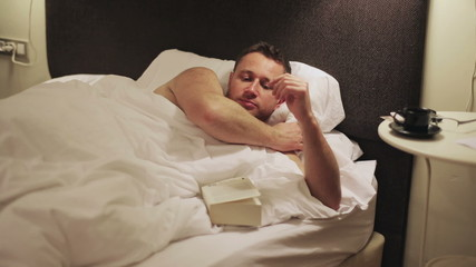 Man finish reading book and going to sleep
