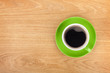 Green coffee cup on wooden table