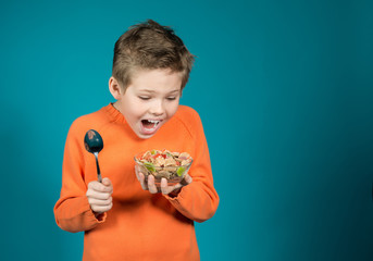 Cute boy eating cereals isolated on blue background
