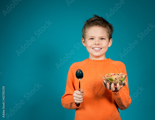 Happy boy eating cereals isolated on blue background