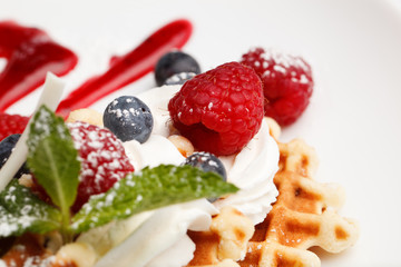 Waffle and cream topped with fresh berries