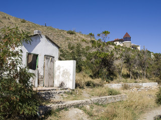 Villa with a tower and destroyed building in the mountains.