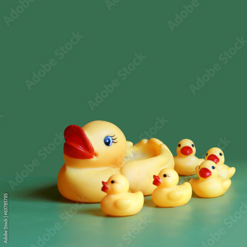 Yellow rubber mom duck with ducklings on green background