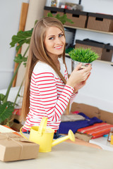 Lifestyle. Attractive girl with grass in pot