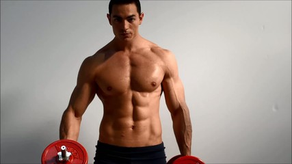 Young handsome male bodybuilder training biceps with dumbbell